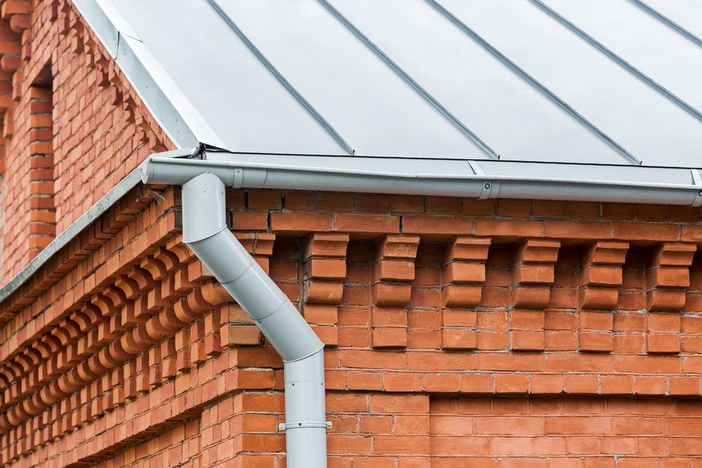 Image of gutters on a brick building to demonstrate our gutter installation services.